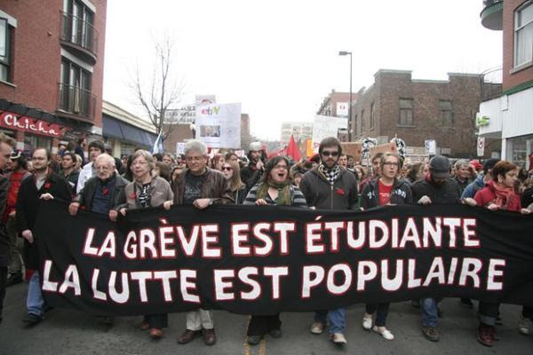 """Marchers in Montreal; banner reads """"The strike is for students, the struggle is for everyone"""" in French"""