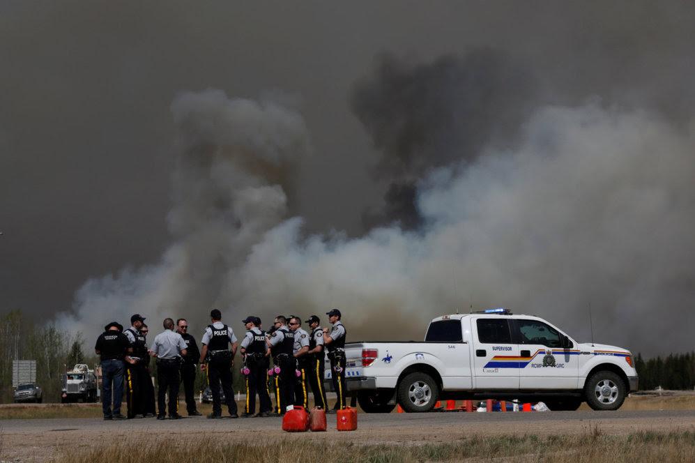 Un grupo de la Real Policía Montada de Canadá se reúne para tomar las medidas pertinentes en una nueva jornada para luchar contra el incendio el día 6 de mayo.