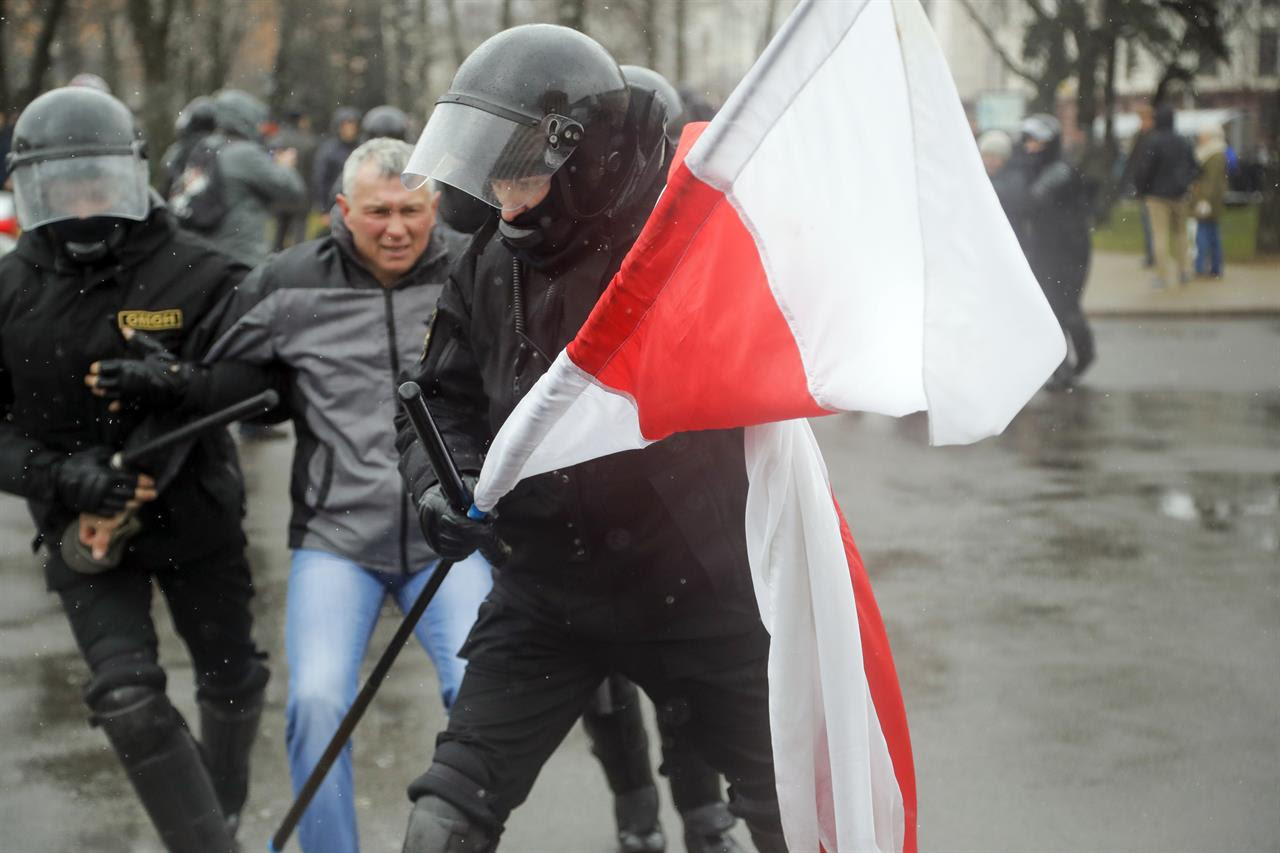 A Belarus policeman carries an opposition flag as other detain a protester during an opposition rally in Minsk, Belarus, Saturday, March 25, 2017. A cordon of club-wielding police blocked the demonstrators' movement along Minsk's main avenue near the Academy of Science. Hulking police detention trucks were deployed in the city center.