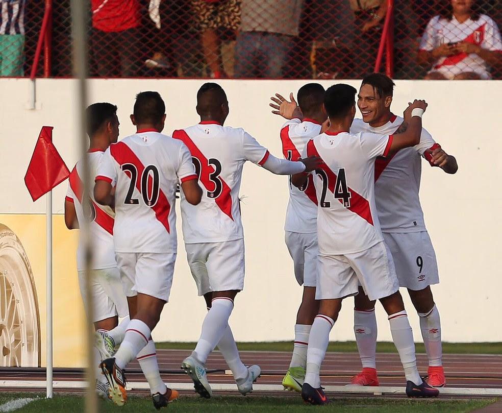 Paolo Guerrero é abraçado por seus companheiros após garantir a vitória contra o Paraguai (Foto: Twitter / @SeleccionPeru )