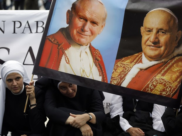 Freiras seguram imagem de Papas no Vaticano neste sábado (26) (Foto: AP Photo/Alessandra Tarantino)