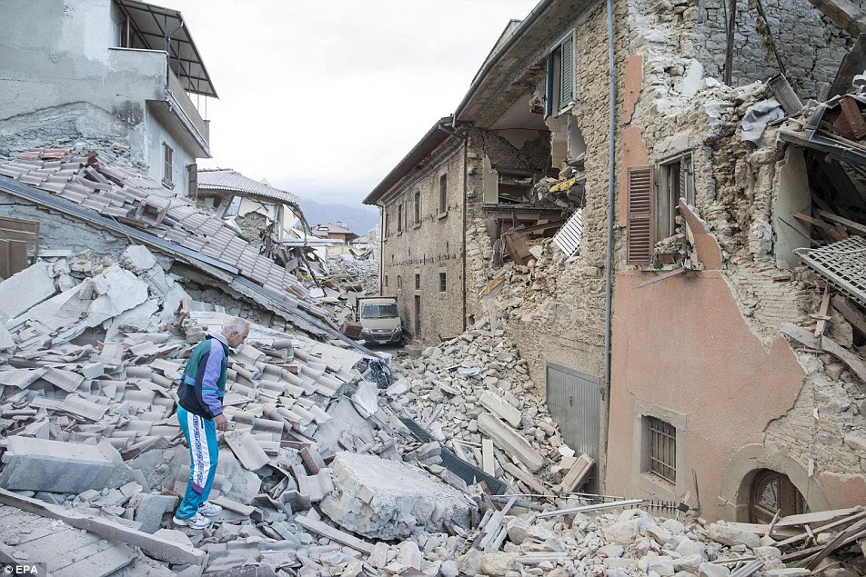 Unimaginable: An elderly man in a tracksuit walks on the rubble of a collapsed buildings in Amatrice. A television aerial can be seen alongside the bricks