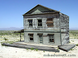 Sitting to the side of the Tombstone Saloon, this fixer-upper appears to have lost two huge sections of its housing, seen on the ground. The sign next to the door reads, ''For Sale.'' Photo copyright 2003-2004 Mike Durrett, all rights reserved.