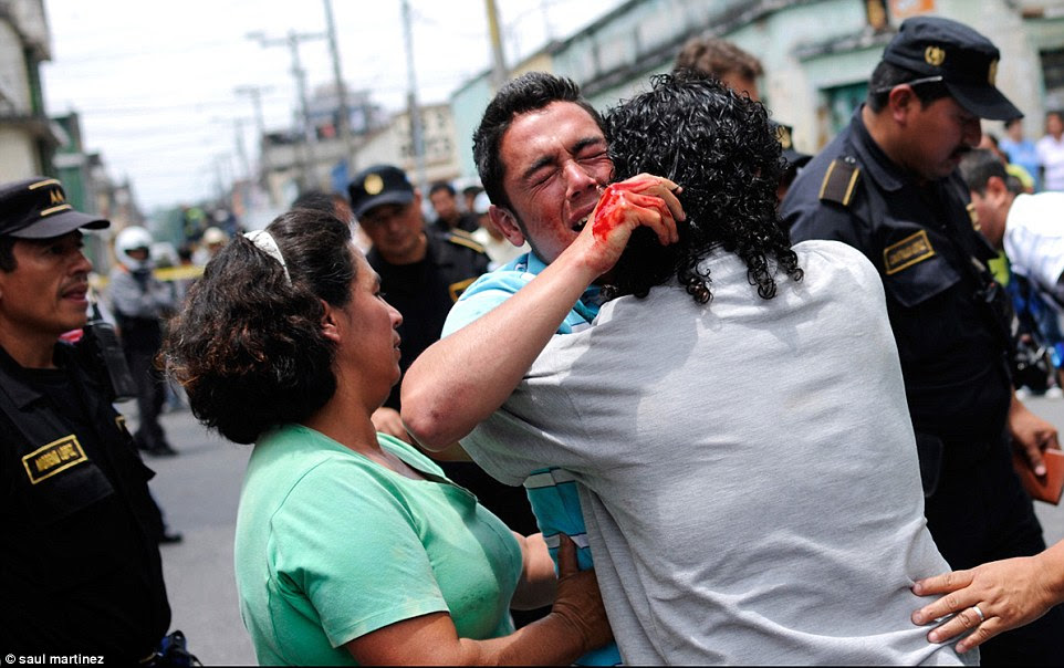 Distraught: A man, his hands covered in blood, weeps after seeing the dead body of his brother, a bus driver, who was killed by gang members.There has been an increase in armed attacks by  gangs on bus drivers and conductors in Guatemala