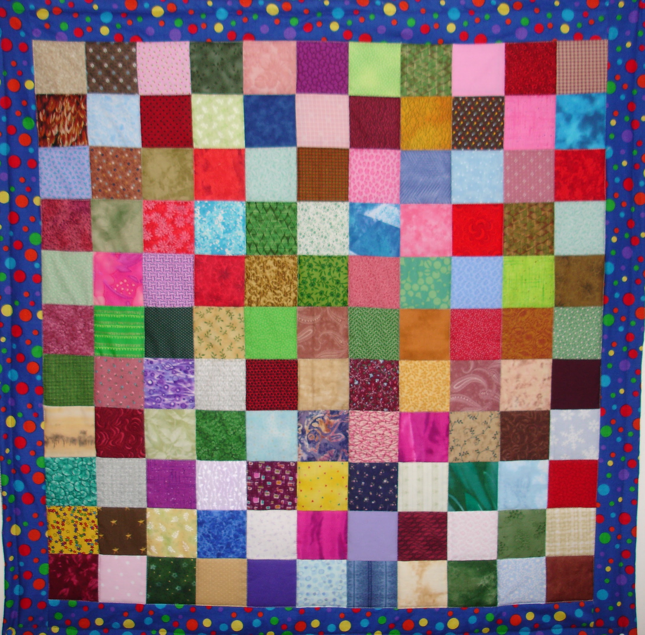bright colorful quilt in small square shape with colorful polkadot frame