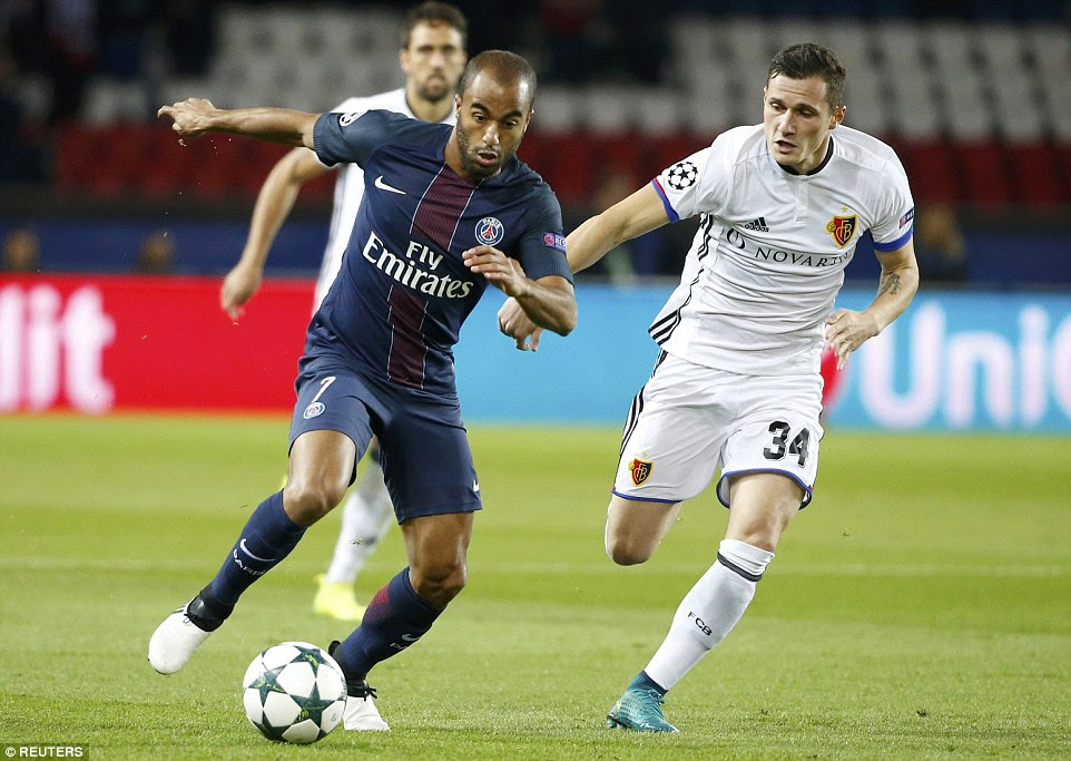 Lucas Moura sprints with possession for the home side under pressure from Basle'sTaulant Xhaka (right)
