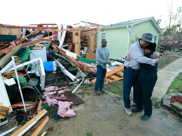 Ao lado de sua casa destruída por um tornado, Phyllis Evans é abraçada por Harvey Payne, em Holly Springs, Mississippi, na quinta (24) (Foto: Reuters/Northeast Mississippi Daily Journal/Thomas Wells )