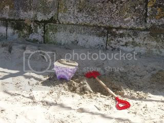 sand,beach,spade,bucket,railings,stone wall,shadows,sunlight