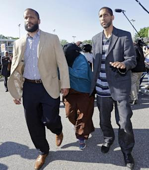 Two men escort the widow, center, of shooting victim …