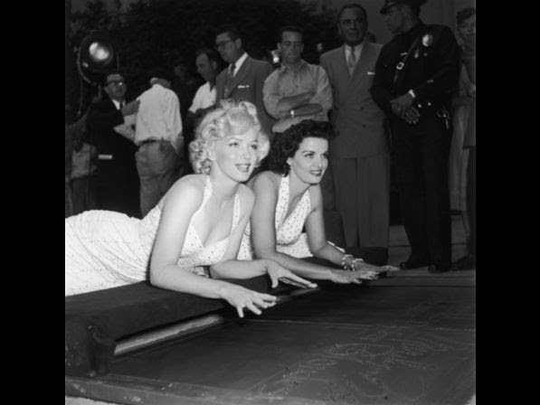 Monroe (left) and Jane Russell lay on their stomachs, about to press their hands into wet cement at Grauman's Chinese Theatre in Hollywood, California, June 26, 1953.