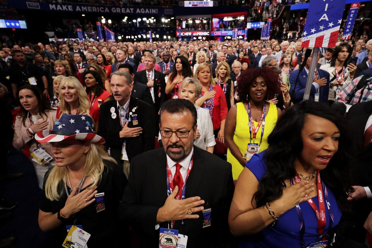 Delegates stand for the Pledge of Allegiance as the last night of the convention began.