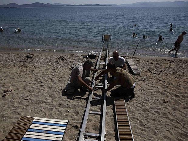 Homens trabalham na instalação do Seatrac na praia de Nea Makri, a leste de Atenas (Foto: Yorgos Karahalis/Reuters)