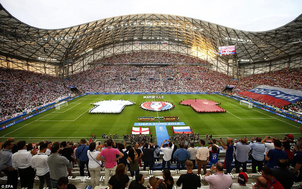 Huge England and Russia shirts are held on the pitch as the players line up for the national anthems ahead of their opening match