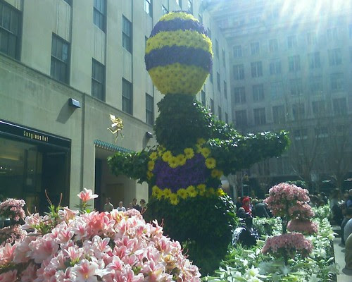 a floral easter bunny with an egg on its nose at rockefeller center.