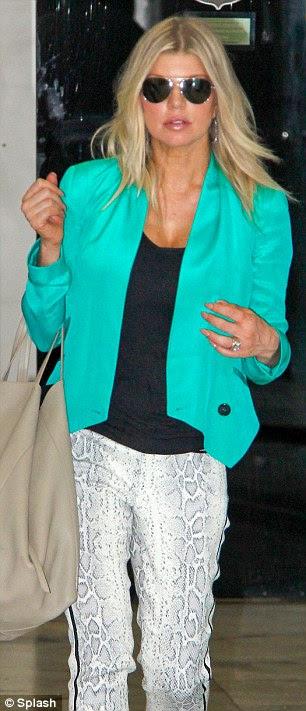 Viajar com estilo: Jennifer usava legging preta e um lenço chunky de seu vôo, enquanto Fergie (R) optou por calças de pele de cobra