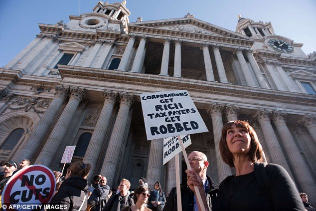 Prepared: Protesters wait for the demonstration to begin outside St Paul's Cathedral