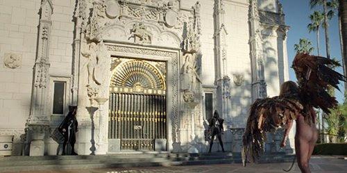 Lucifer-Gaga llega delante del castillo de Hearst y es recibido por hombres encapuchados.