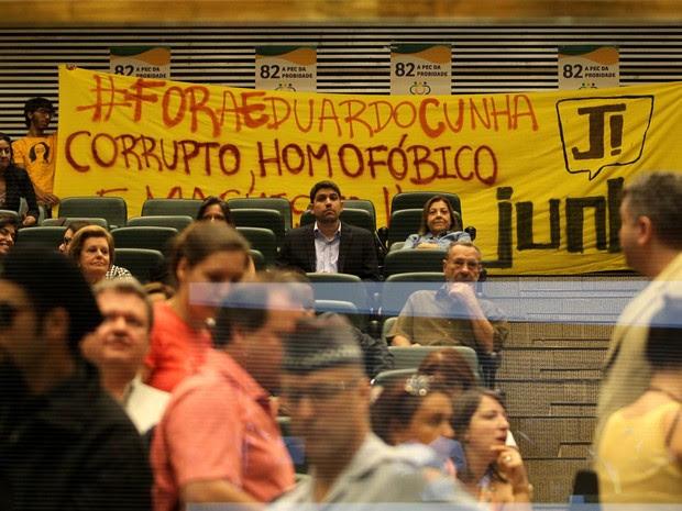 O Presidente da Câmara dos Deputados, Eduardo Cunha, acompanhado de vários deputados federais, é recebido com protesto de um grupo de manifestantes na Assembleia Legislativa de São Paulo. Na faixa, ele é chamado de 'corrupto, homofóbico' (Foto: Hélvio Romero/Estadão Conteúdo)