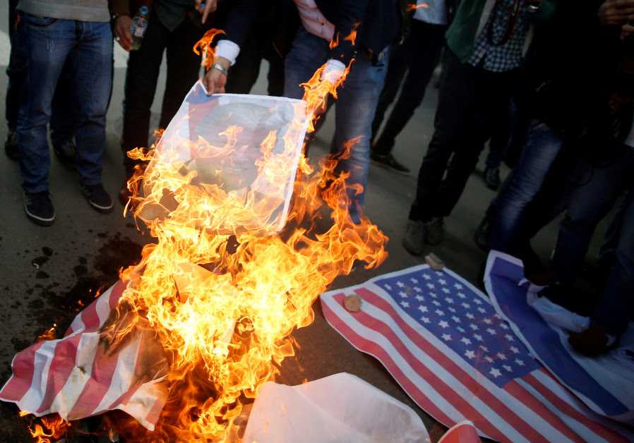 Palestinian protesters burn a poster depicting US President Donald Trump and a US flag