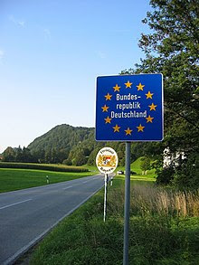"""Eine """"Schengen-Grenze"""" zwischen zwei EU-Staaten, hier in Tirol bei Kufstein (Österreich) in Fahrtrichtung Bayern (Deutschland): Es gibt keine Grenzkontrollposten an der Staatsgrenze, nur ein blaues Schild mit einem Sternenkranz um den Namen des EU-Staates. Bildquelle: Wikipedia Deutschland"""