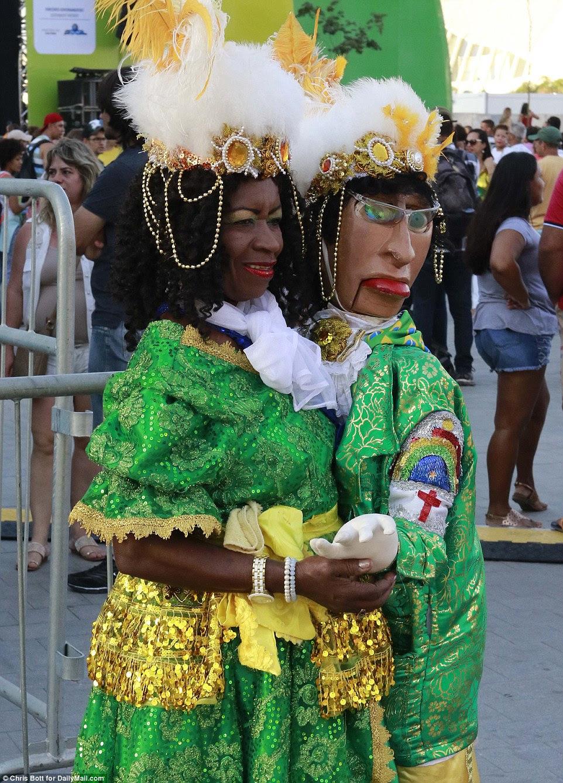 Uma mulher, em um traje verde e dourado elaborado, realizou um manequim com roupas combinando, enquanto esperava para a cerimônia