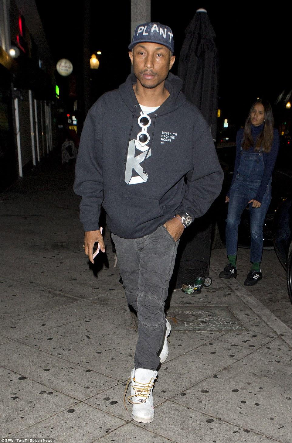 estrela na moda: Pharell parecia utilizar a sua elegante como ele se dirigiu para a festa em um hoodie simples e botas de trabalho brancas