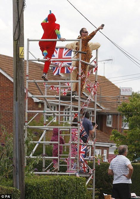 Spectators wearing fancy dress take to a scaffolding as the Tour de France passes through Bannister Green near Felsted in Essex