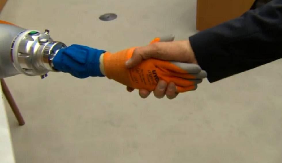 Un hombre da la mano a un robot en la Global Robot Expo de Madrid.