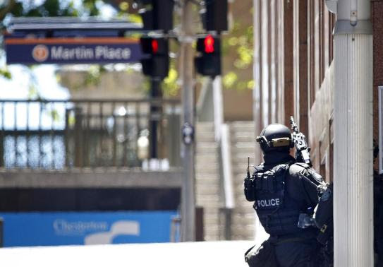 A New South Wales state police officer is seen at a corner near Lindt cafe in Martin Place, where hostages are being held, in central Sydney December 15, 2014. REUTERS-Jason Reed