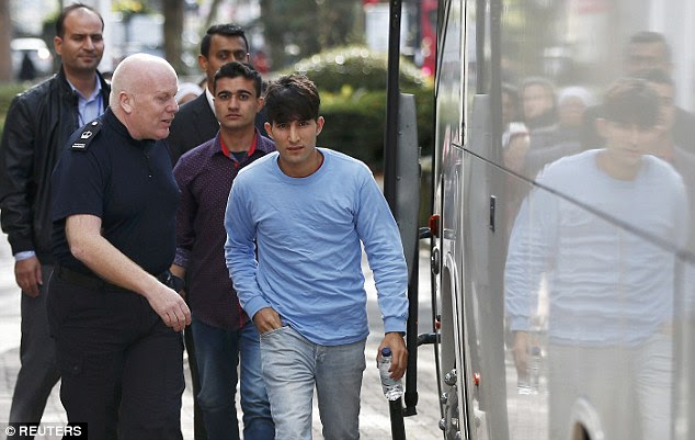 Two of the youngsters, one wearing a long-sleeved blue top and another in a dark patterned shirt, are escorted off the bus and taken to the Home Office base