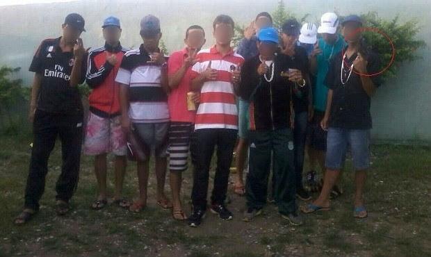 Grupo reunido para foto; à direita, suspeito exibe uma arma para a foto (Foto: Divulgação/Polícia Civil)