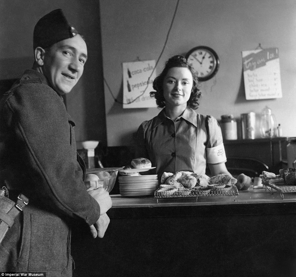 Down time: A soldier orders a cup of tea in the Forces Canteen at Victoria Station in 1942. The soldier pictured was the butler of a close friend of photographer Cecil Beaton