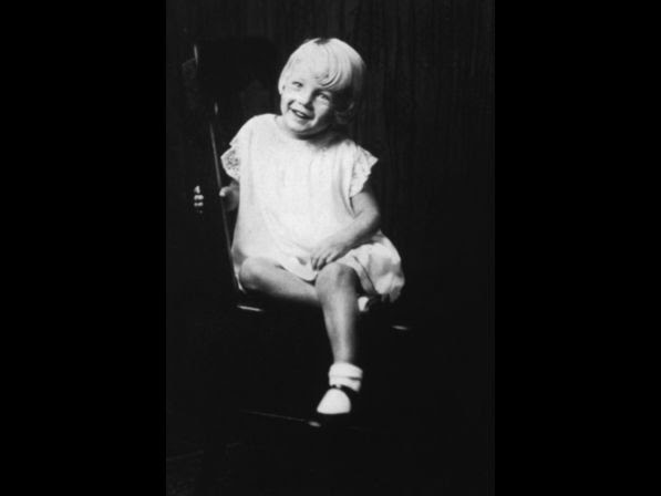 Monroe at age 5, sitting in a wooden chair.