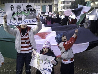 """Young Syrian girls hold Arabic placard read:""""I am proud to be Homsi, left, and I am breathing freedom, center,"""" during a demostration against the Syrian regime, in Homs"""