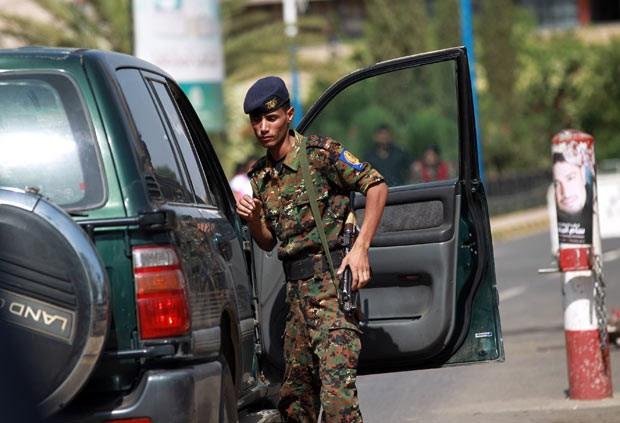 Policial iemenita vasculha carro na entrada do aeroporto da capital, Sanaa, nesta quarta-feira (7) (Foto: AFP)