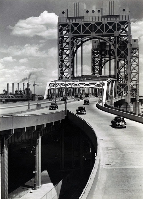 Triborough Bridge, East 125th Street approach, Manhattan. Six cars visible on approach and bridge, street below, bridge superstructure, right, smoke-stacks of Hell Gate Con-Ed. power plant, left.