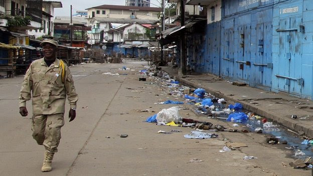 A Liberian soldier walks along a deserted street with shops closed in Monrovia, Liberia
