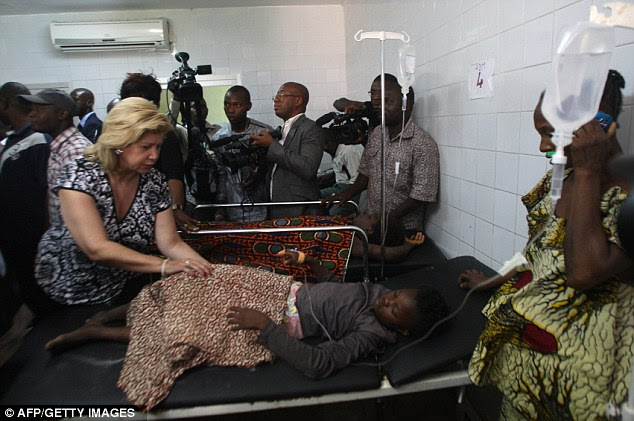 Dominique Ouattara (left), wife of President of The Ivory Coast Alassane Ouattara, stands next to a child who injured in a stampede which has killed at least 61 people at firework's display in Abidjan