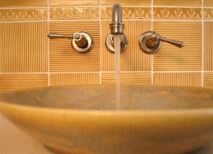 Ceramic Ridge Tiles with accent strip and vessel sink create this Bathroom backsplash