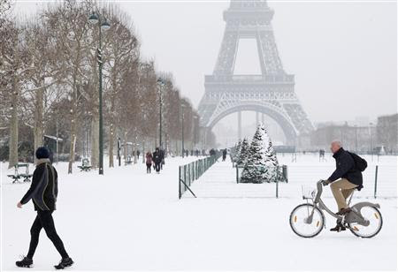 A man rides a Velib self-service public bicycle as he makes his way along a snow-covered area at the Champs de Mars near the Eiffel Tower in Paris January 19, 2013. REUTERS-John Schults