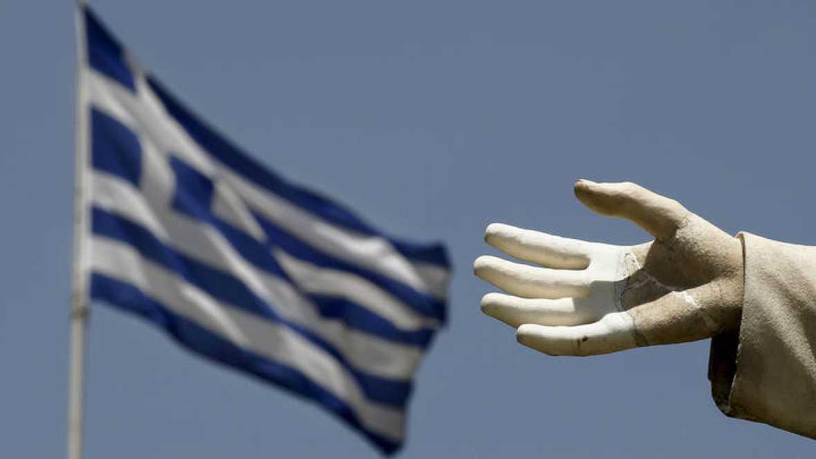 La mano abierta de una estatua en primer plano y una bandera griega detrás