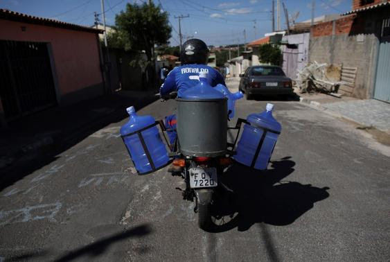 A vendor rides on his motorcycle carrying water bottles, which he supplies to houses as eight-month rationing of water continues as a result of a record drought, in Itu, October 27, 2014.  REUTERS-Nacho Doce
