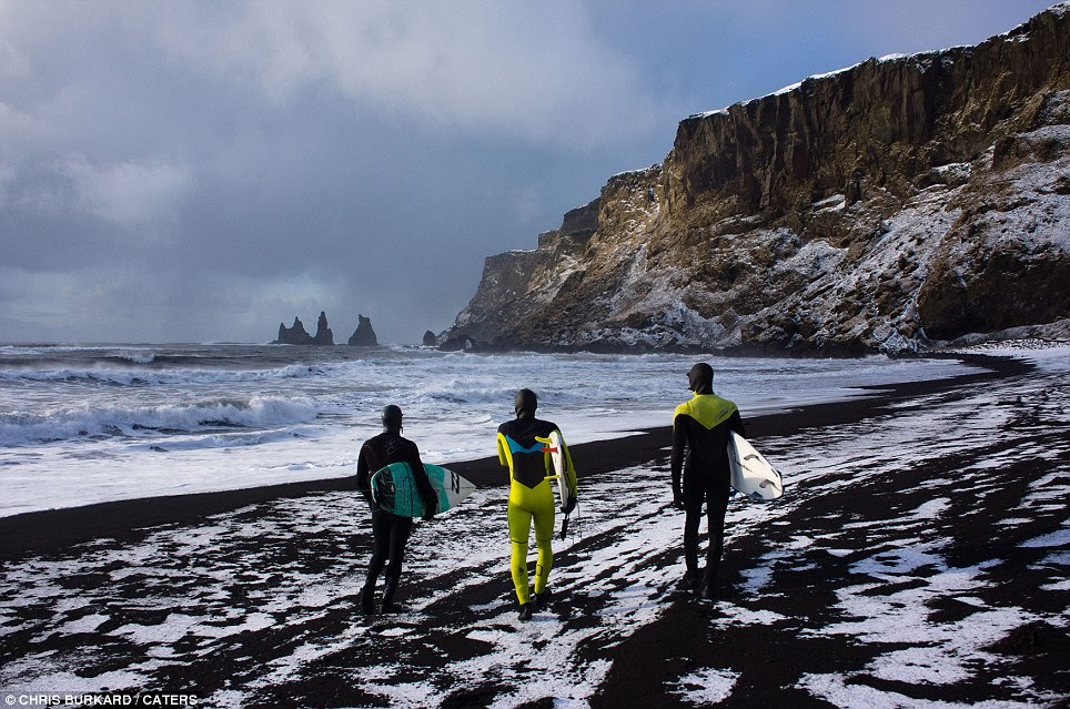 The three surfers survey the waters. They had to walk through the ice-covered road to the beach and through snow as high as his waist - all just to reach the water's edge