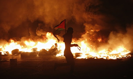 A protester holds a Palestinian flag at a barricade of burning tyres in clashes with Israeli troops