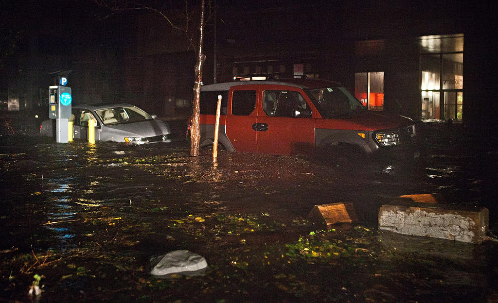 Floodwater covers cars in the Financial District of New York Monday night.