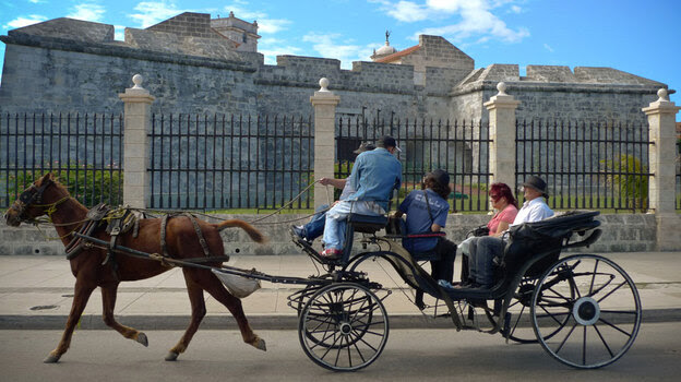 Tourists ride in a horse-drawn carriage on a Havana street in January.