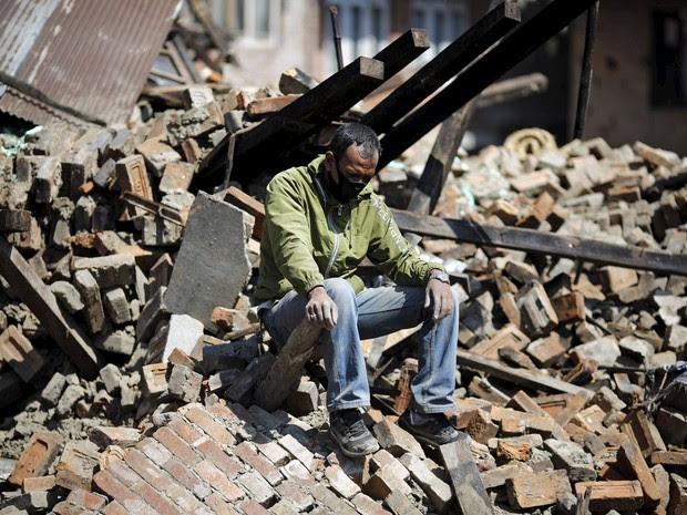 Um homem senta-se sobre os escombros de sua casa danificada após o terremoto de sábado, em Bhaktapur (Foto: REUTERS/Adnan Abidi)