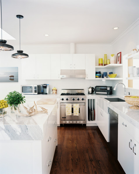 Kitchen - Marble countertops and white cabinetry in a bright kitchen