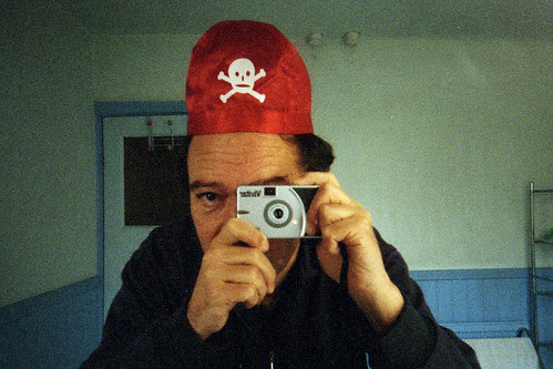 reflected self-portrait with Vivitar Ultra Wide & Slim camera and skull & cross-bones hat by pho-Tony