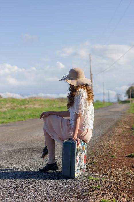 フリー写真 旅行鞄に腰掛けながら通りかかる車を待つ女性でアハ体験